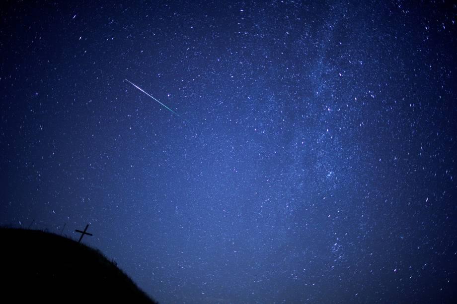 Meteoro risca o céu com a Via Láctea visível acima da colina de Leeberg durante a chuva de meteoros Perseidas em Grossmugl, na Áustria - 12/08/2018