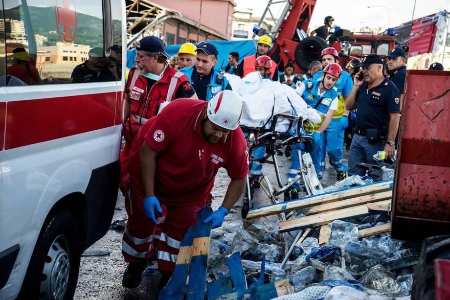 Corpo é carregado por equipes de resgate enquanto aguardam a chegada de ambulância, após queda de ponte em Gênova, na Itália - 14/08/2018