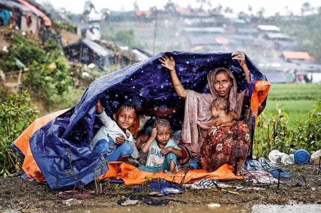 Família de rohingyas protege-se da chuva, em Bangladesh: refúgio no país vizinho.
