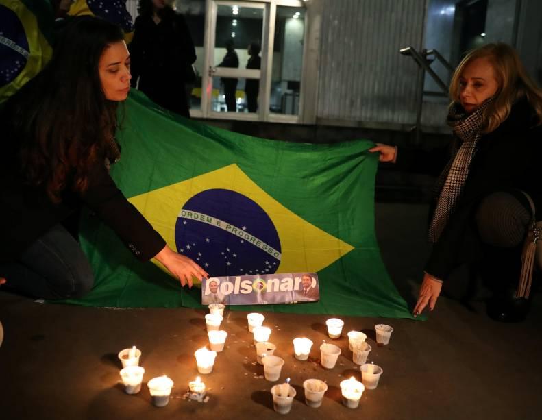 Mulheres esticam uma bandeira do Brasil em frente ao hospital da Santa Casa, em Juiz de Fora, Minas Gerais em homenagem ao presidenciável Jair Bolsonaro, após um atentado com faca - 06/09/2018