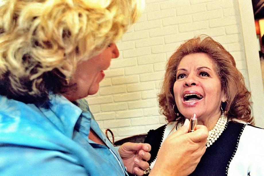 A apresentadora Silvia Poppovic passa batom na boca da cantora Ângela Maria durante almoço de Raul Cortez