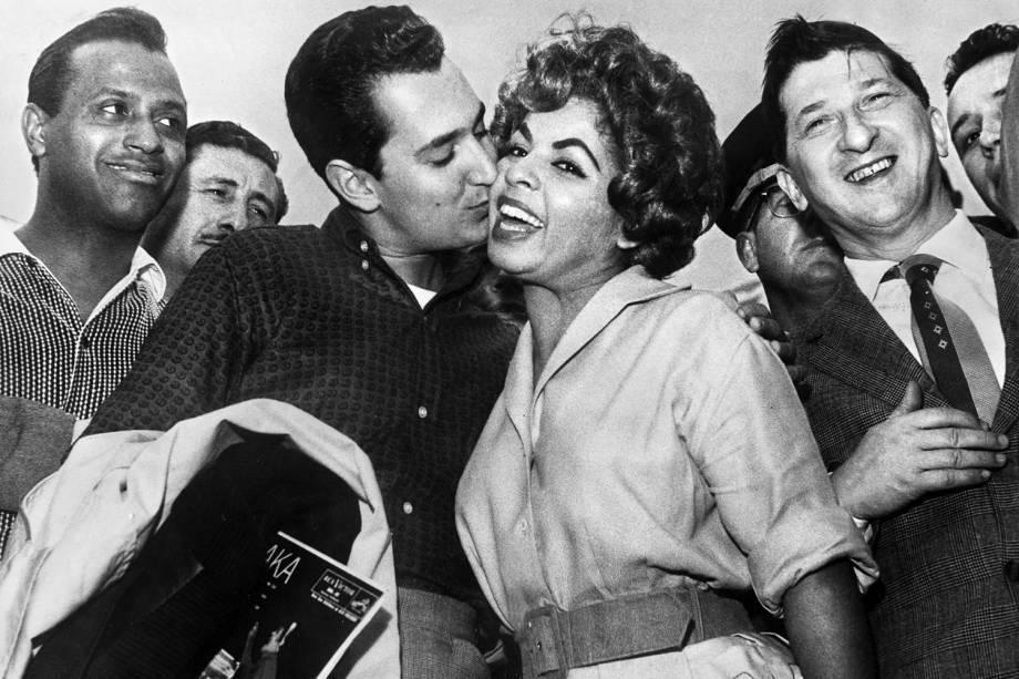 O cantor e compositor americano Neil Sedaka beija a cantora brasileira Ângela Maria, observado pelo cantor Carlos Gonzaga em São Paulo - 08/11/1959