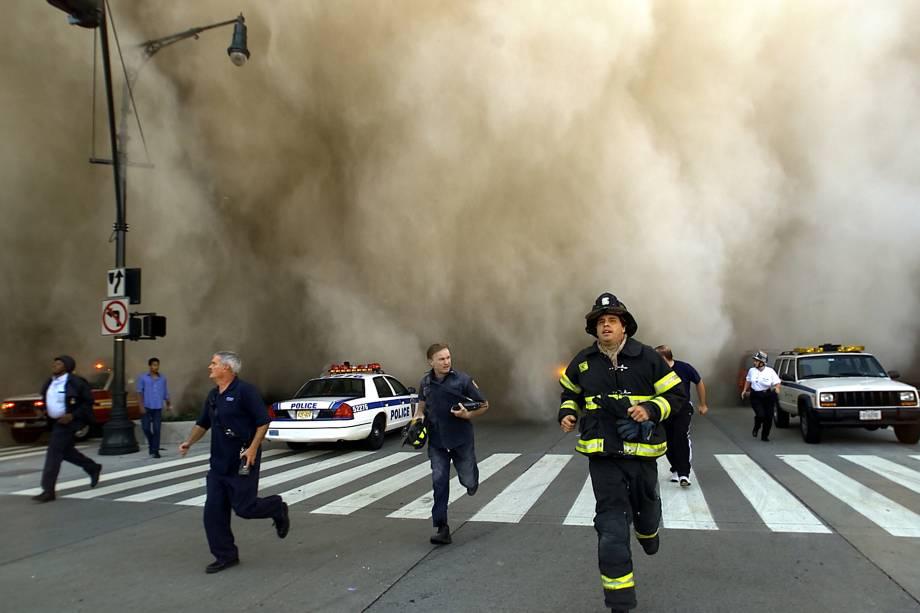 Policiais e bombeiros correm de uma enorme nuvem de fumaça no momento da queda de uma das torres do World Trade Center - 11/09/2001