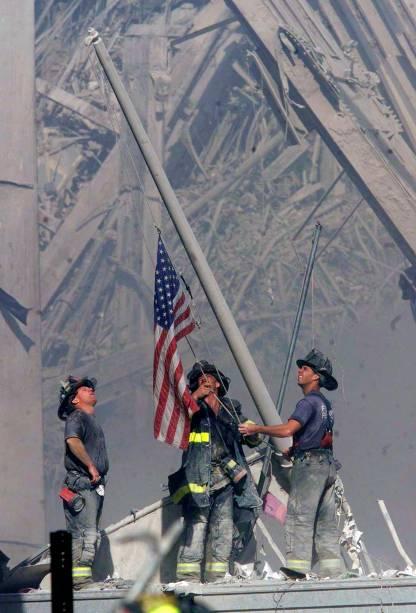 Bombeiros levantam uma bandeira dos Estados Unidos em meio aos escombros do World Trade Center após ataque terrorista - 11/09/2001