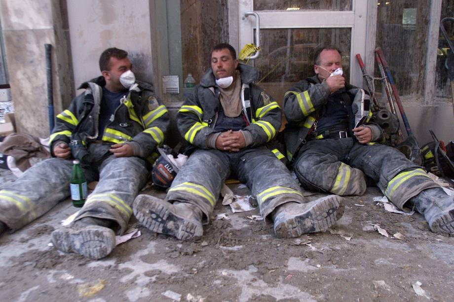 Bombeiros exaustos descansam na Broadway durante a busca por sobreviventes após atentado terrorista no World Trade Center - 11/09/2001