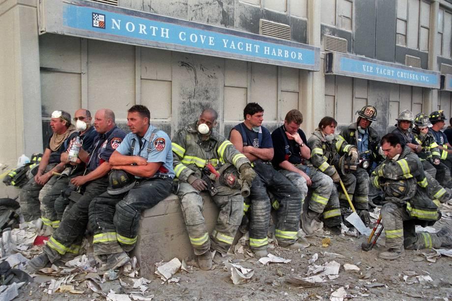 Bombeiros descansam durante operação de resgate das vítimas após o colapso das torres do World Trade Center, alvo de ataque terrorista - 11/09/2001