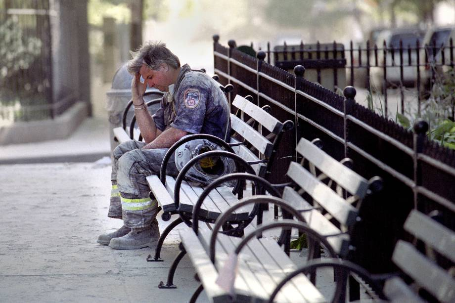 Bombeiro faz uma pausa em um banco duante as operações de resgate após o colapso das torres gêmeas do World Trade Center alvo de um ataque terrorista - 11/09/2001