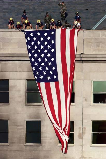 Bombeiros e militares estendem uma bandeira dos Estados Unidos sobre o prédio do Pentágono a poucos metros da área danificada pelo ataque  terrorista - 11/09/2001