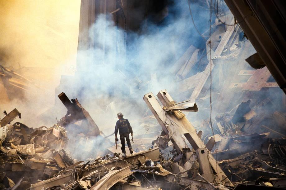 Bombeiro caminha nos escombros das Torres Gêmes destruídas durante ataque terrorista em 11 de setembro de 2001 em Nova York