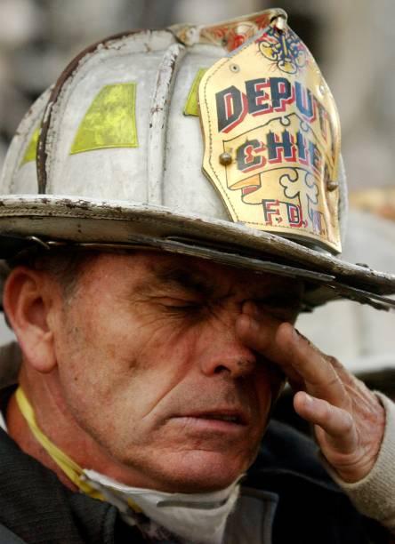 Bombeiro esfrega os olhos no cenário do desastre do World Trade Center em Nova York - 14/09/2001