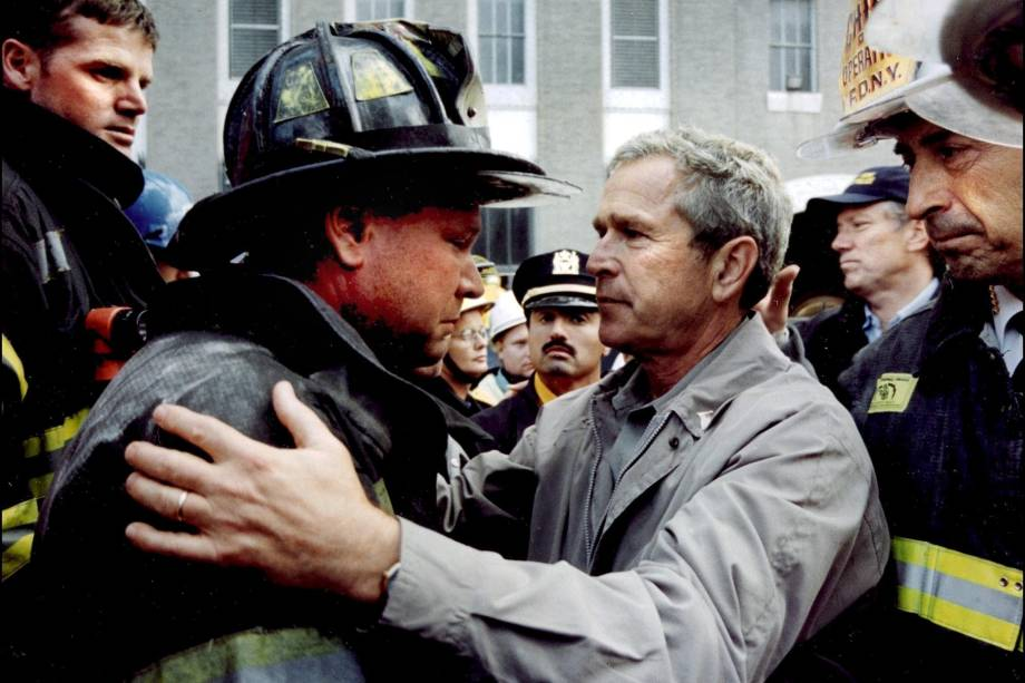 O presidente George W. Bush conforta o bombeiro Lenard Phelan, que perdeu seu irmão, também bombeiro durante as operações de resgate no World Trade Center - 14/09/2001