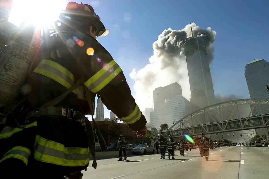 Bombeiros caminham em direção a uma das torres do World Trade Center em Nova York, antes que ela desabasse após ser atingida por um avião