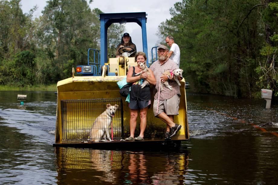 Homem usa seu trator para transportar sua família e animais de estimação em meio a enchente provocada pela passagem do furacão Florence em Burgaw, na Carolina do Norte - 17/09/2018
