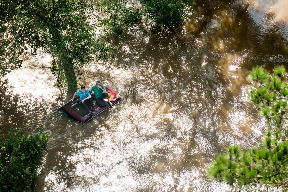 Homens sentam-se no teto de um carro coberto de água em Wallace, na Carolina do Sul - 17/09/2018