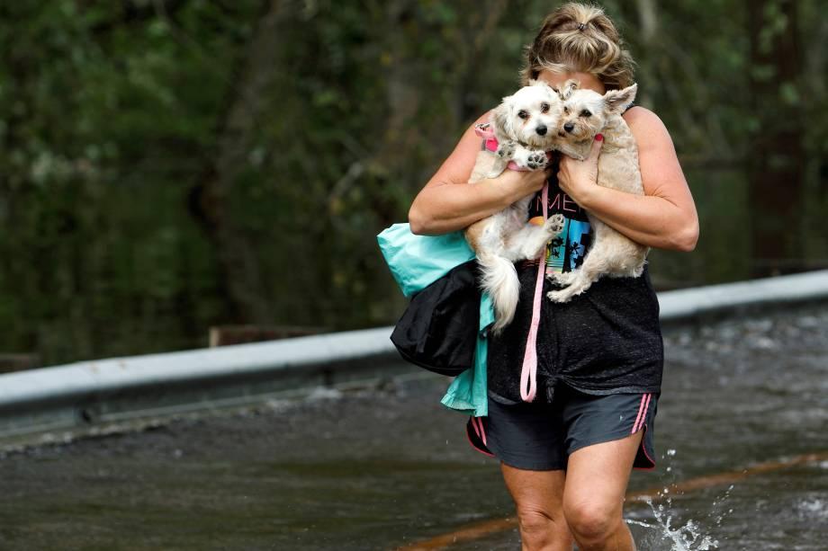 Mulher abraça seus cães de estimação após ser retirada de uma região inundada em Burgaw, na Carolina do Norte - 17/09/2018