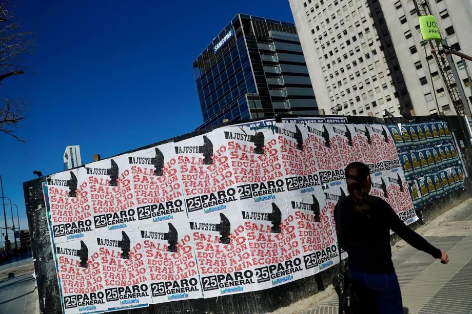 Pedestre caminha próxima de cartazes fixados em muro, durante greve geral em Buenos Aires, capital da Argentina - 25/09/2018