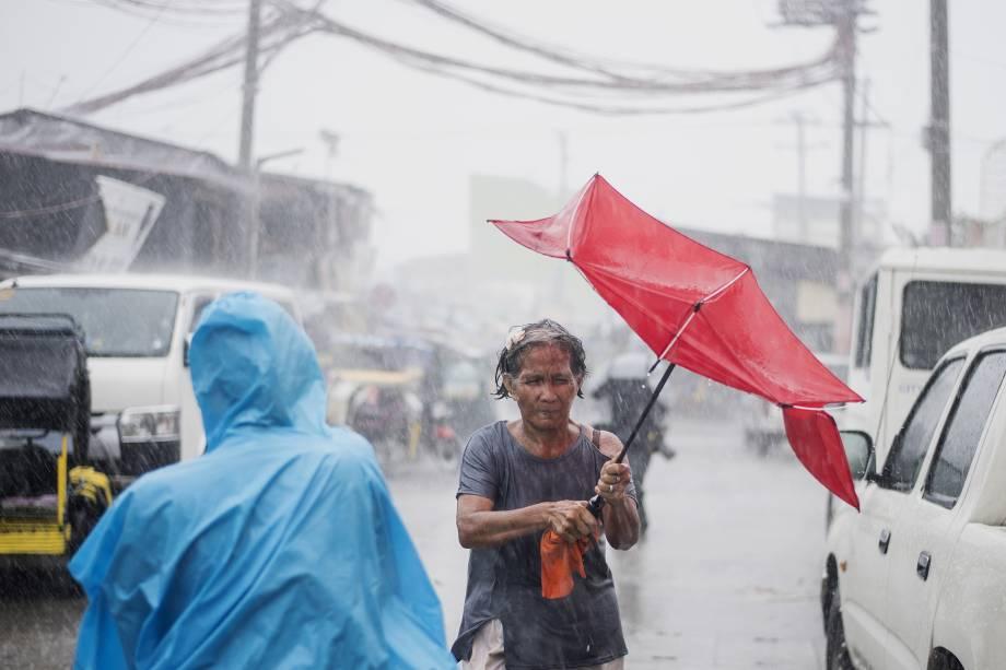 Mulher tem seu guarda-chuva destruído durante as fortes tempestades causadas pelo supertufão Mangkhut em Manila nas Filipinas - 15/09/2018