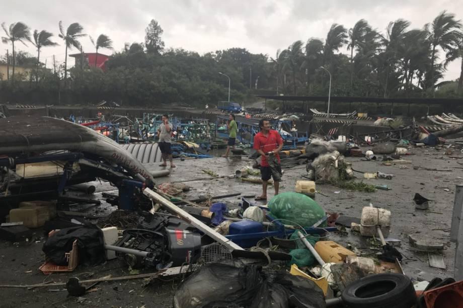 Moradores caminham entre os destroços do porto de pesca de Shang Wu, no condado de Taitung, leste de Taiwan - 15/09/2018