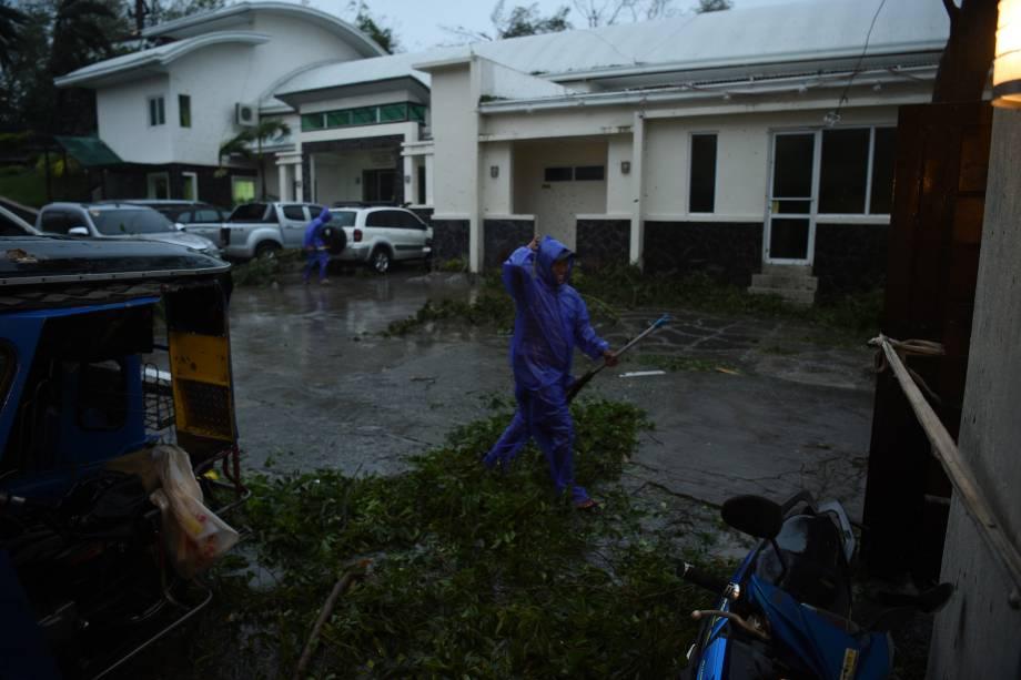 Trabalhadores removem galhos de uma árvore derrubado pelos ventos do supertufão Mangkhut que atingiu a cidade de Tuguegarao, província de Cagayan, ao norte de Manila nas Filipinas - 15/09/2018