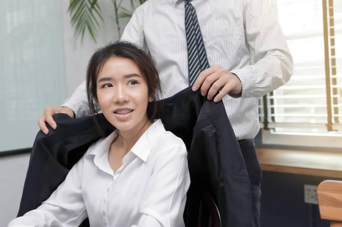 Homem veste seu paletó em uma funcionária