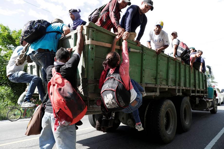 Imigrante hondurenha é puxada para conseguir subir em um caminhão que toma rumo aos Estados Unidos, em direção à fronteira mexicana, em Chiquimula, na Guatemala - 24/10/2018