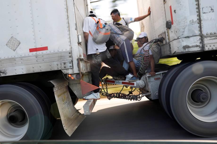 Imigrantes são vistos entre os eixos de um caminhão na estrada para Mapastepec de Huixtla, México, enquanto seguem para os Estados Unidos - 24/10/2018