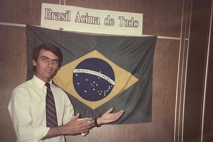 Jair Bolsonaro posa para foto com a bandeira do Brasil na frente de seu gabinete na Câmara dos Deputados