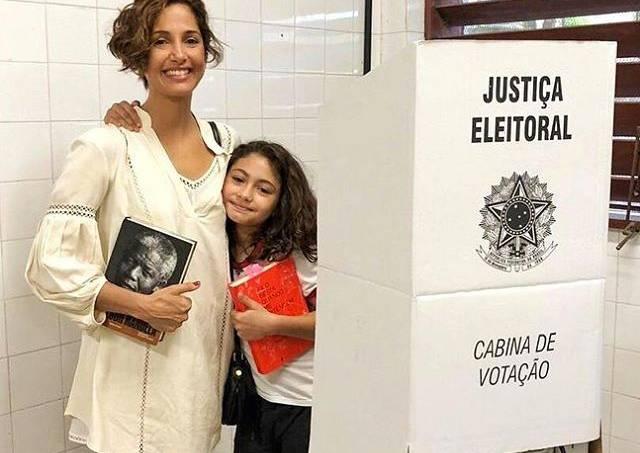 Camila Pitanga votando com livro