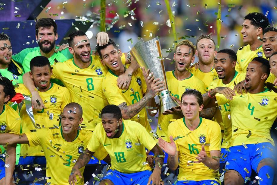 Neymar e Roberto Firmino (centro) erguem o troféu do Superclássico das Américas, após a Seleção Brasileira vencer a Argentina por 1 a 0 - 16/10/2018