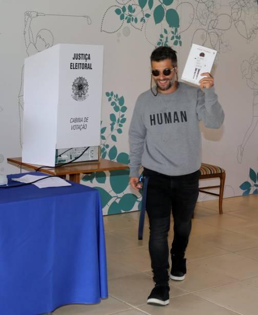 Bruno Gagliasso votando com livro