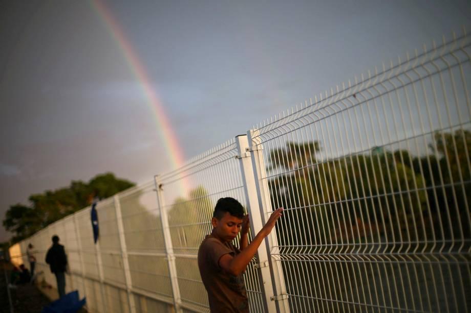 Imigrante que aguarda para seguir viagem até os Estados Unidos é fotografado junto com um arco-iris em Ciudad Hidalgo, no México - 21/10/2018