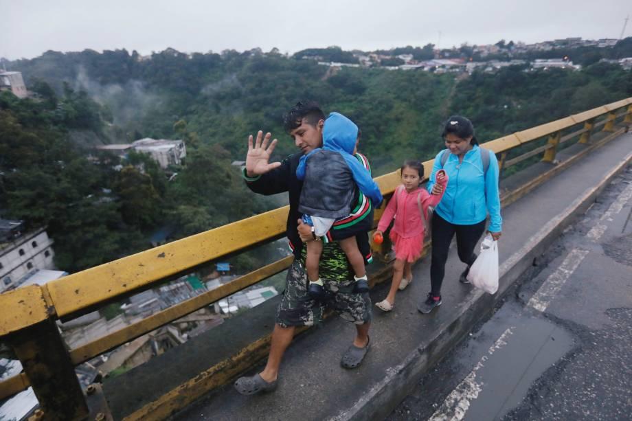 Imigrantes hondurenhos, parte de uma caravana que tenta chegar aos Estados Unidos, caminham em uma ponte durante sua viagem na Cidade da Guatemala, Guatemala - 18/10/2018