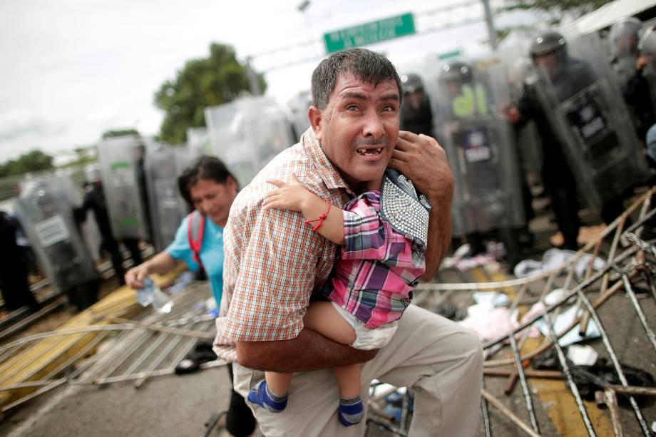 Imigrante hondurenho protege seu filho depois que outros imigrantes, parte de uma caravana que tentava chegar aos Estados Unidos, invadiram um posto fronteiriço em Ciudad Hidalgo, México - 20/10/2018
