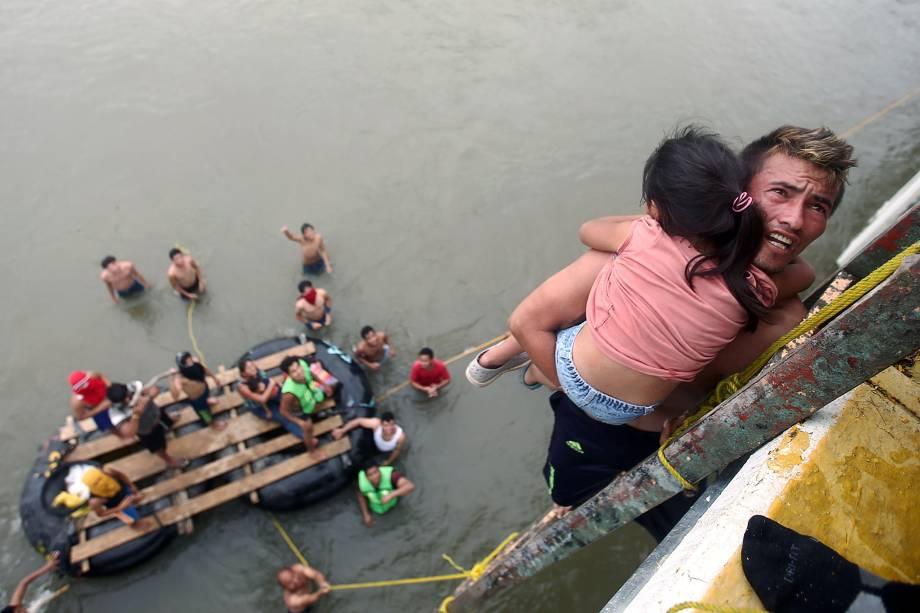 Imigrante hondurenho segura uma criança ao descer de uma ponte que liga México e Guatemala para evitar o posto fronteiriço em Ciudad Hidalgo, no México - 20/10/2018