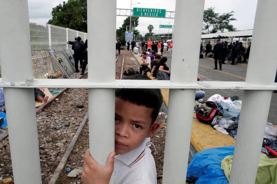 Menino hondurenho, parte de uma caravana que tenta chegar aos Estados Unidos, é fotografado na ponte que liga México e Guatemala em Tecun Uman - 20/10/2018