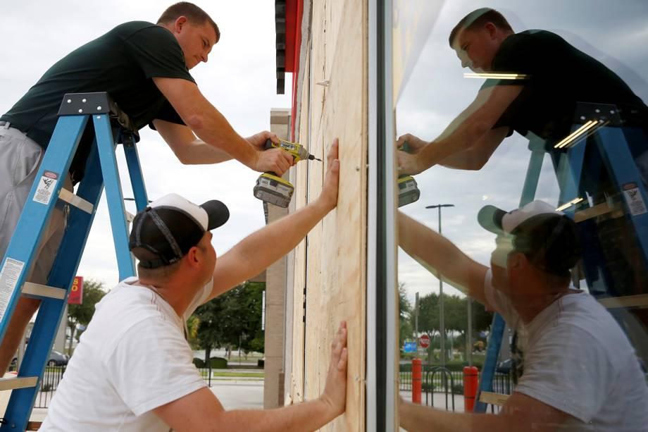 Homens colocam tapumes de madeira em estabelecimento comercial, antes da passagem do furacão Michael em Destin, cidade localizada no estado americano da Flórida - 09/10/2018