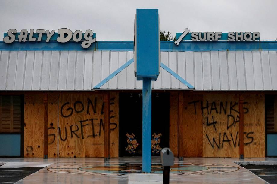 Uma mensagem de agradecimento às grandes ondas é vista em uma proteção de madeira nas portas de uma loja de surfe, em Panama City Beach, na Flórida, antes da chegada do furacão Michael - 10/10/2018