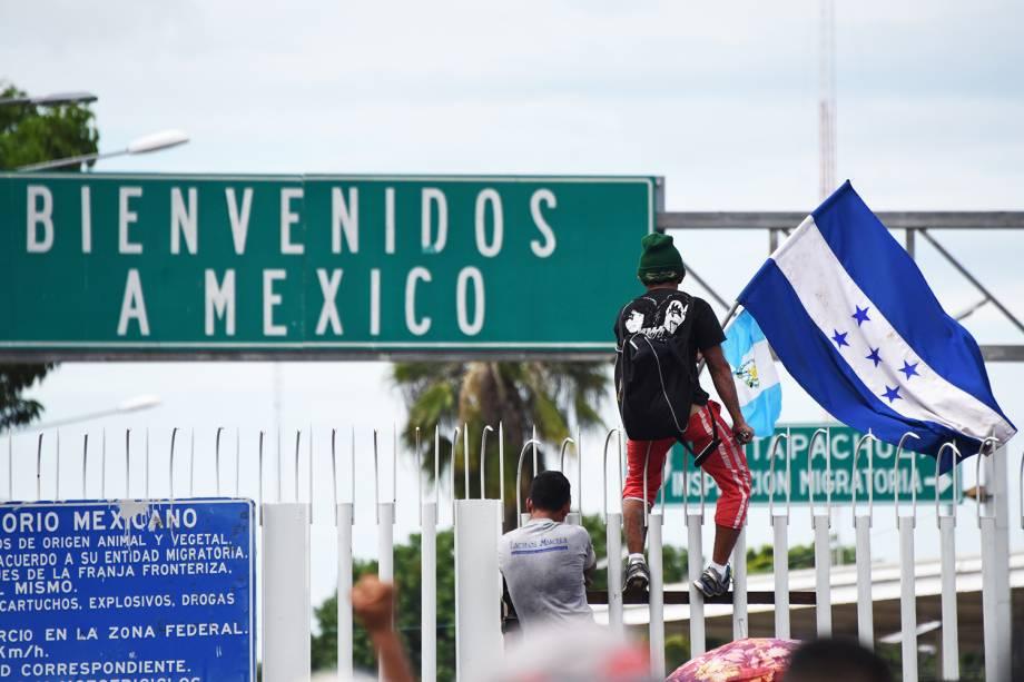 Migrante hondurenho é visto com bandeira, próximo da fronteira entre a Guatemala e o México, no território de Ciudad Tecun Uman - 19/10/2018