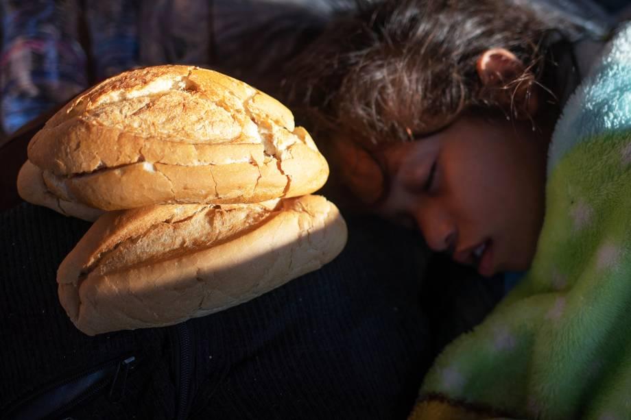 Garota dorme próxima de pão que foi doado para imigrantes hondurenhos, nos arredores da cidade mexicana de Tapachula - 22/10/2018