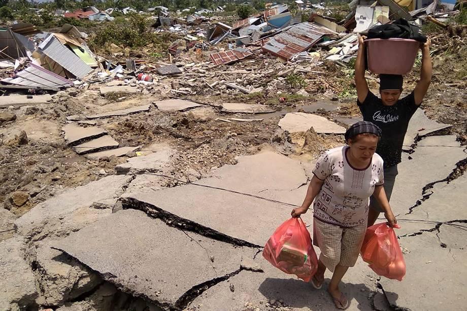 Residentes de Palu, a cidade mais afetada pelo terremoto seguido de tsunami em Sulawesi, na Indonésia, carregam mantimentos após os tremores - 29/09/2018