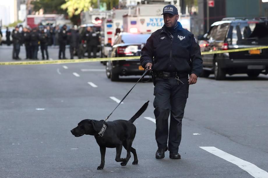 Policial caminha com um cão farejador do lado de fora do prédio Time Warner Center, após uma ameaça de bomba, em Nova York - 24/10/2018
