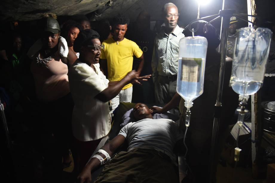 Mulher ora por homem ferido após terremoto no Hospital Imaculada Concepção em Port-de-Paix, Haiti - 07/10/2018