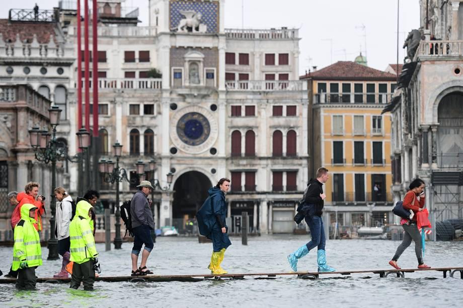 Pessoas andam por uma ponte improvisada na Praça de São Marcos, em Veneza, Itália, após uma inundação devido à alta de 150 centímetros da maré - 29/10/2018