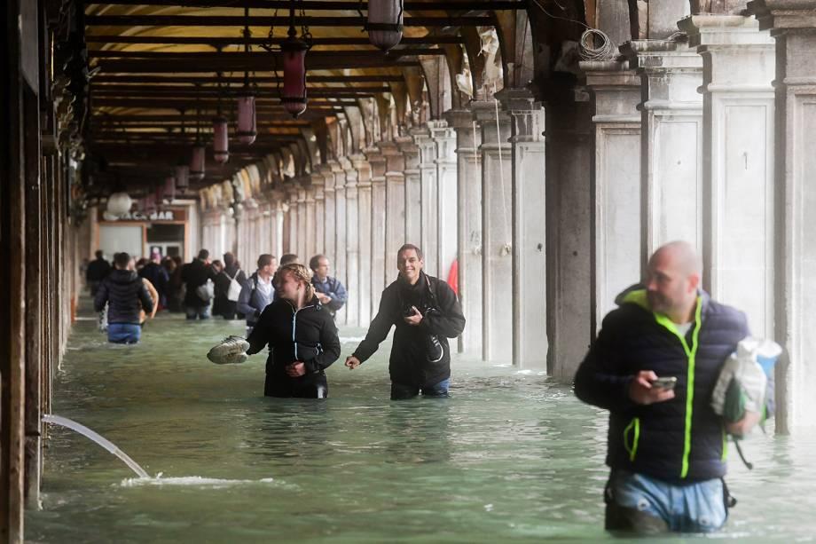 Com água na região da cintura, pedestres andam pelos arcos da Praça de São Marcos, em Veneza, na Itália - 29/10/2018