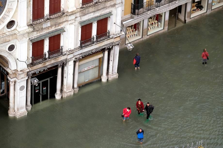 Pessoas caminham com água pelos joelhos na Praça de Marcos, em Veneza, na Itália - 29/10/2018