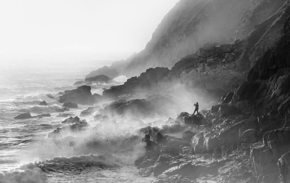 """Pescador. Em Porth Nanven, Cornualia, Inglaterra - """"Houveram fortes ventos de oeste por alguns dias, o que resultou em uma ondulação no Atlântico muito maior do que o previsto. Eu estava feliz em sentar nas rochas e fotografar as ondas, mas então alguma mágica aconteceu... um pescador apareceu nas rochas, no quadro; Eu não pude acreditar na minha sorte."""""""