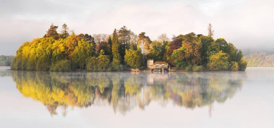 """Isolamento. Derwentwater, Inglaterra - """"A Ilha e sua casa de barcos se tornaram as estrelas do espetáculo quando o sol matutino adicionou um calor e profundidade às cores das árvores."""""""
