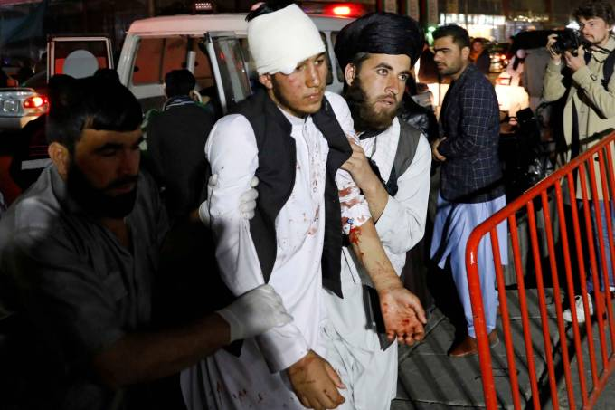 Afghan men carry an injured person to a hospital after a suicide attack in Kabul