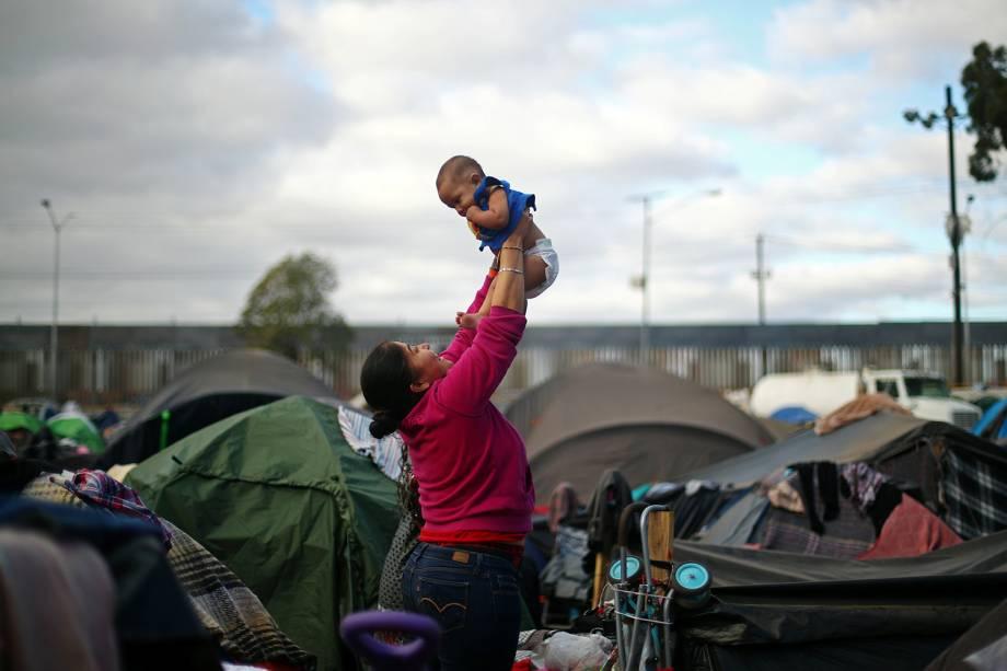 Migrante ergue bebê em acampamento montado na fronteira entre o México e os Estados Unidos, na cidade de Tijuana - 28/11/2018