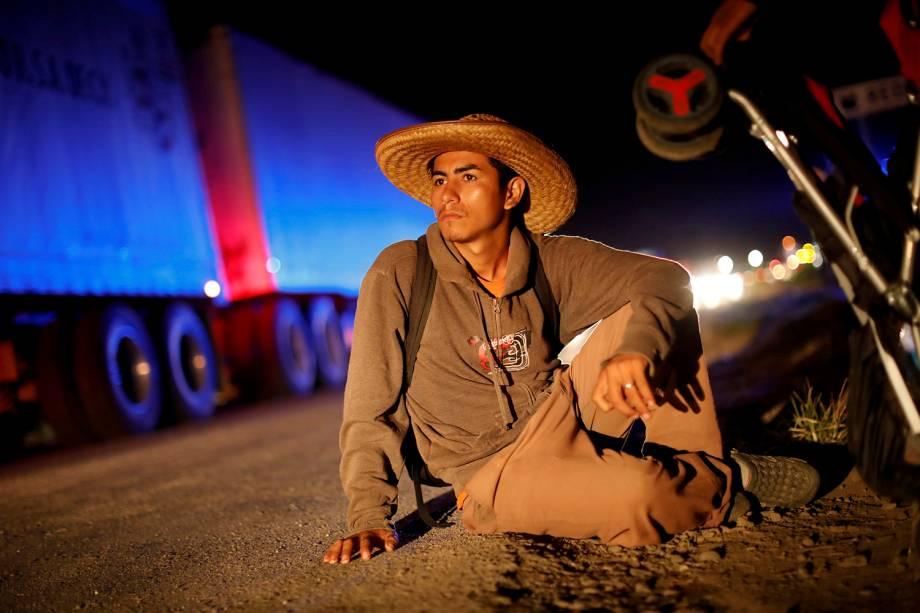 Cristian Israel, parte de uma caravana que viaja da América Central em rota para os Estados Unidos, espera para pegar carona depois de descansar em um acampamento improvisado em Matias Romero Avendano, México - 10/11/2018